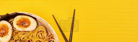 top view of seafood ramen near chopsticks on yellow surface, panoramic shot