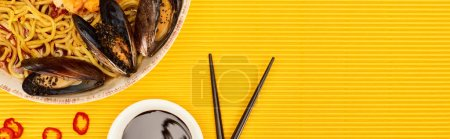 Photo for Top view of seafood ramen near soy sauce and chopsticks on yellow surface, panoramic shot - Royalty Free Image
