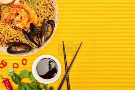 Photo for Top view of seafood ramen near fresh ingredients, soy sauce and chopsticks on yellow surface - Royalty Free Image