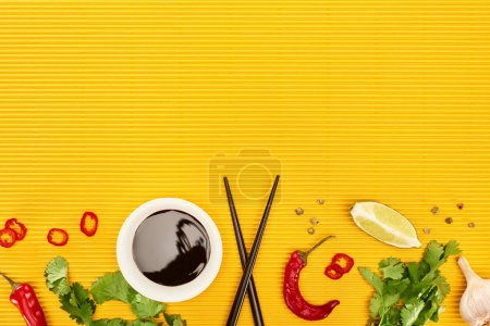 Photo for Top view of fresh spices, vegetables, soy sauce and chopsticks on yellow surface - Royalty Free Image