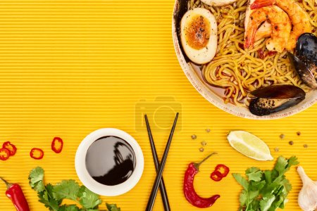 Photo for Top view of seafood ramen near fresh ingredients and chopsticks on yellow surface - Royalty Free Image