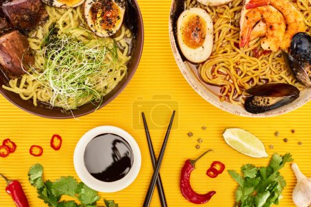 Photo for Top view of seafood and meat ramen near fresh ingredients, soy sauce and chopsticks on yellow surface - Royalty Free Image