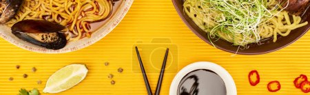 Photo for Top view of seafood and meat ramen near fresh ingredients, soy sauce and chopsticks on yellow surface, panoramic shot - Royalty Free Image