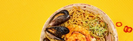 Photo for Top view of seafood ramen on yellow surface, panoramic shot - Royalty Free Image