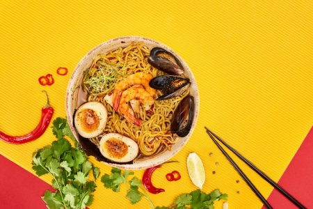 Photo for Top view of seafood ramen near fresh ingredients and chopsticks on yellow and red surface - Royalty Free Image