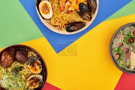 Photo for Top view of spicy seafood and meat ramen on multicolored surface - Royalty Free Image