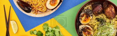 Photo for Top view of spicy seafood and meat ramen near fresh ingredients and chopsticks on multicolored surface, panoramic shot - Royalty Free Image