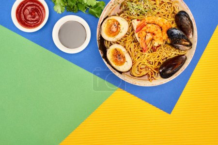 Photo for Top view of spicy seafood ramen near chili and soy sauces on multicolored surface - Royalty Free Image