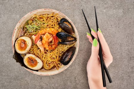 Photo for Cropped view of woman holding chopsticks near spicy seafood ramen on grey surface - Royalty Free Image