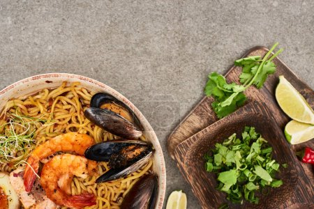 Photo for Top view of spicy seafood ramen near fresh ingredients on grey surface - Royalty Free Image