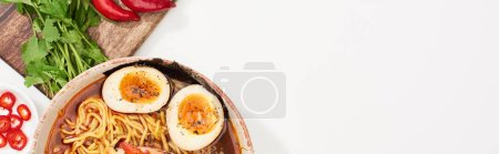 Photo for Top view of spicy ramen near fresh ingredients on white surface, panoramic shot - Royalty Free Image