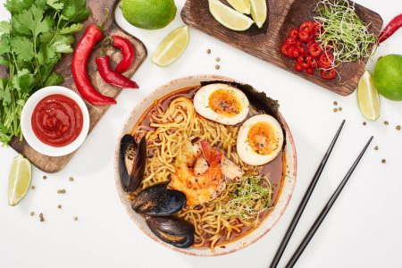 Photo for Top view of spicy seafood ramen near fresh ingredients and chopsticks on white surface - Royalty Free Image