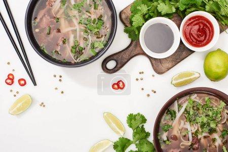 Photo pour Vue d'ensemble du pho dans les bols près des baguettes, de la lime, du chili, des sauces de soja et de la coriandre sur fond blanc - image libre de droit