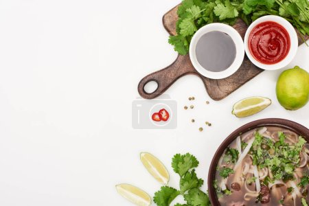 Photo for Top view of pho in bowl near chopsticks, lime, chili and soy sauces and coriander on white background - Royalty Free Image
