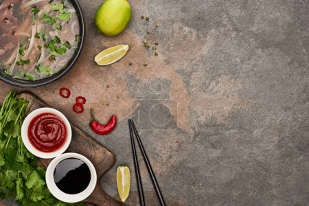 Photo for Top view of pho in bowl near chopsticks, lime, chili and soy sauces and coriander on stone background - Royalty Free Image