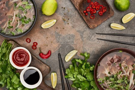 Photo for Top view of pho in bowls near chopsticks, lime, chili and soy sauces and coriander on stone background - Royalty Free Image