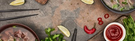 Photo for Top view of pho in bowls near chopsticks, lime, chili and soy sauces and coriander on stone background, panoramic shot - Royalty Free Image
