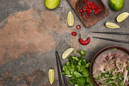 Photo for Top view of pho in bowl near chopsticks, lime, chili and coriander on stone background - Royalty Free Image