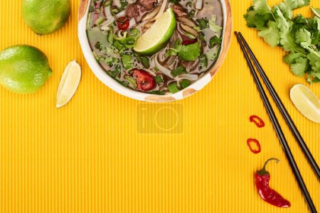Photo for Top view of pho in bowl near chopsticks, lime, chili and coriander on yellow textured background - Royalty Free Image
