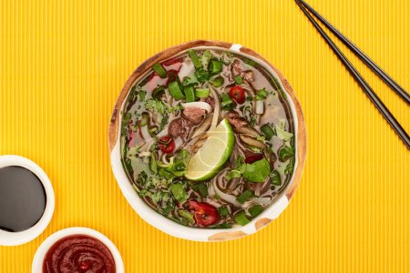 top view of pho in bowl near chopsticks, chili and soy sauces on yellow textured background