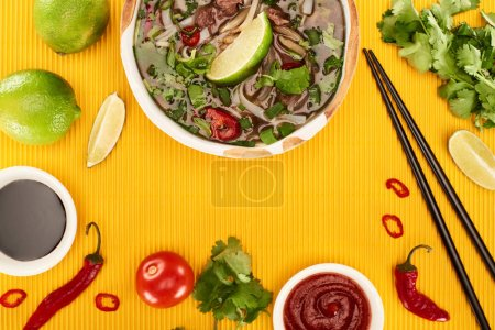 Photo for Top view of pho in bowl near chopsticks, lime, chili and soy sauces and coriander on yellow textured background - Royalty Free Image