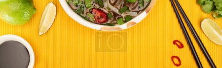 Photo for Top view of pho in bowl near chopsticks, lime, soy sauce and coriander on yellow textured background, panoramic shot - Royalty Free Image