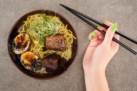 cropped view of woman holding chopsticks near ramen with egg and beef in bowl on grey background