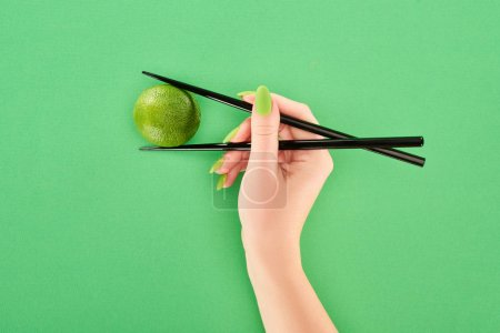 Photo for Cropped view of woman holding whole lime with chopsticks on green background - Royalty Free Image