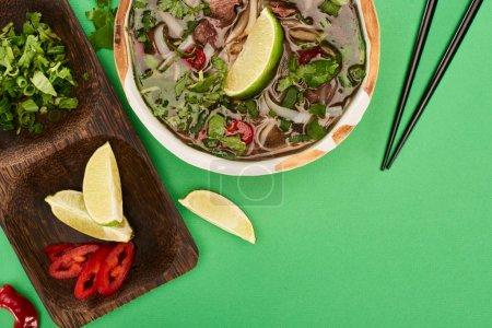 Photo pour Vue du dessus du pho dans un bol près des baguettes et planche en bois avec chaux, chili et coriandre sur fond vert - image libre de droit