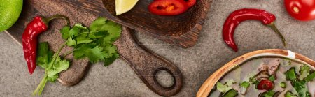 Photo for Top view of pho in bowl near lime, chili and coriander on wooden cutting board on grey background, panoramic shot - Royalty Free Image