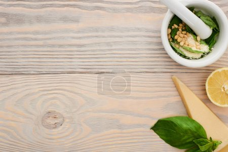 Photo for Top view of pesto sauce raw ingredients in pounder on wooden table - Royalty Free Image
