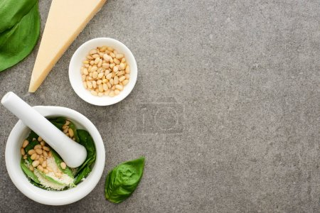 Photo for Top view of pesto sauce raw ingredients and pounder on grey surface - Royalty Free Image