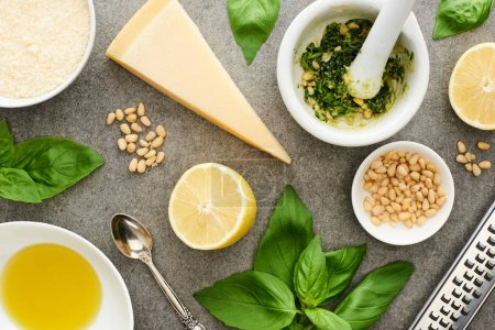 Photo for Top view of pesto sauce raw ingredients and cooking utensils on grey surface - Royalty Free Image