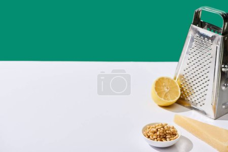 Photo for Lemon, parmesan, pine nuts and grater on white table isolated on green - Royalty Free Image