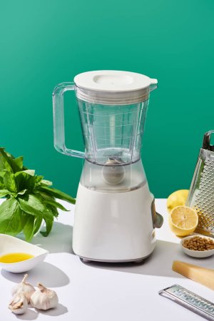 Photo for Pesto sauce raw ingredients and food processor on white table isolated on green - Royalty Free Image