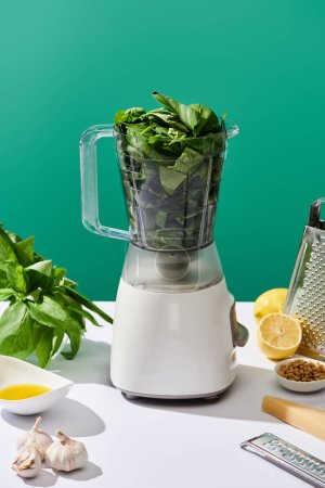 Photo for Pesto sauce raw ingredients and food processor with basil leaves on white table isolated on green - Royalty Free Image