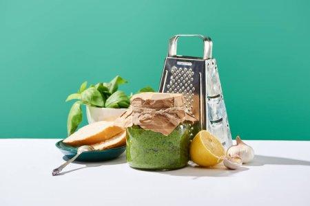 Photo pour Sauce pesto en pot près des ingrédients, baguette et râpe sur table blanche isolée sur vert - image libre de droit