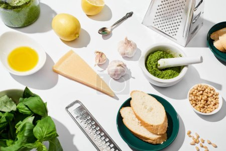 Photo for Pesto sauce near ingredients, graters and bread on white background - Royalty Free Image