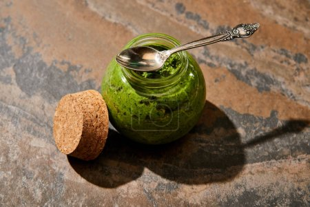 pesto sauce in glass jar with spoon near cork on stone surface