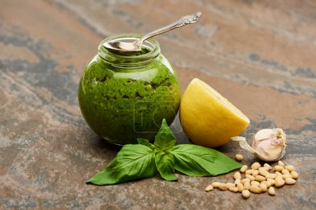 pesto sauce in glass jar with spoon near ingredients on stone surface