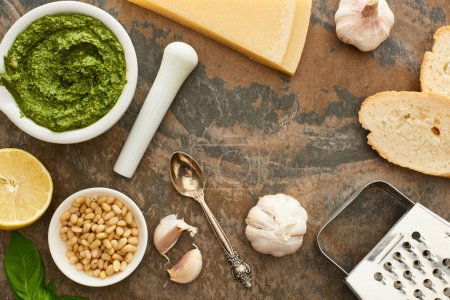 Photo for Top view of pesto sauce, ingredients and bread on stone surface - Royalty Free Image