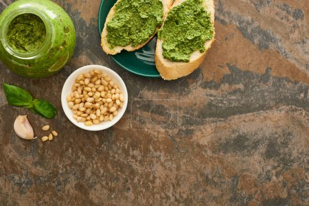 Photo for Top view of baguette slices with pesto sauce on plate near fresh ingredients on stone surface - Royalty Free Image
