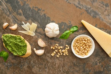 Photo for Top view of baguette slice with pesto sauce near fresh ingredients on stone surface - Royalty Free Image