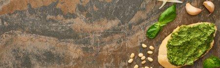 Photo pour Vue de dessus de la tranche de baguette avec sauce pesto près des ingrédients frais sur la surface de la pierre, vue panoramique - image libre de droit