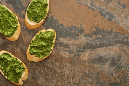 Photo for Top view of baguette slices with delicious pesto sauce on stone surface - Royalty Free Image