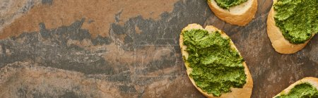 top view of baguette slices with delicious pesto sauce on stone surface, panoramic shot