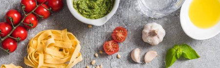 Photo for Top view of raw Pappardelle near tomatoes, garlic, basil, pine nuts, olive oil, water and pesto sauce on grey surface, panoramic shot - Royalty Free Image