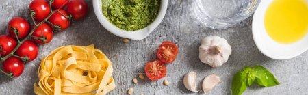 Photo pour Vue du dessus de la Pappardelle crue près des tomates, ail, basilic, pignons de pin, huile d'olive, eau et sauce pesto à la surface grise, panoramique - image libre de droit