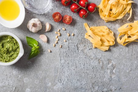Photo for Top view of raw Pappardelle near tomatoes, garlic, basil, pine nuts, olive oil, water and pesto sauce on grey surface - Royalty Free Image