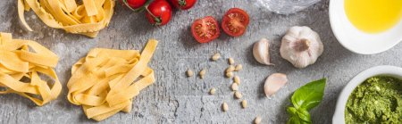 Photo pour Top view of raw Pappardelle near tomatoes, garlic, basil, pine nuts, olive oil, water and pesto sauce on grey surface, panoramic shot - image libre de droit